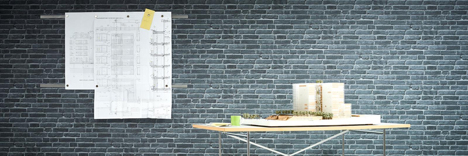 CAD + Reprofolien. Modell eines Gebäudes auf einem Schreibtisch und eine Konstruktionszeichnung auf einer grauen Wand.