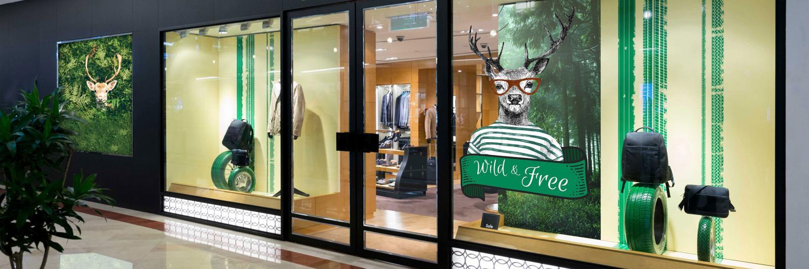 Druckmedien selbstklebend für Werbeschilder - Schaufenster Boutique mit grüner Werbung und Hirsch mit Brille und T-Shirt
