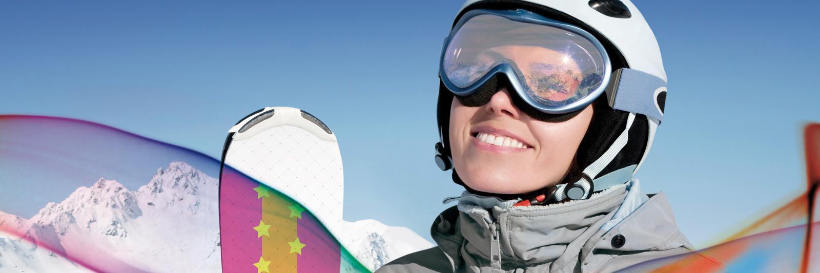 Sublimationspapiere für Transferdruck - Snowboardfahrerin mit weißem Helm im Gebirge schaut in die Sonne