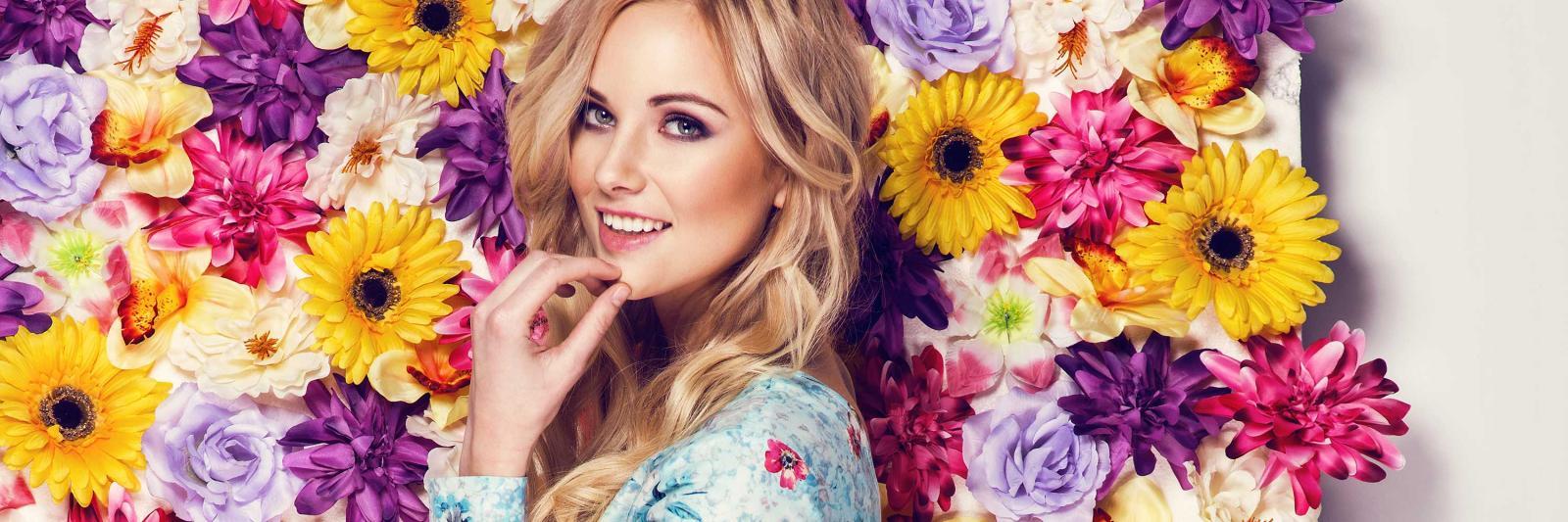 Transferpapiere für Sublimation auf flexible Substrate - blonde Frau mit Blumenkleid vor einer Wand aus Blüten