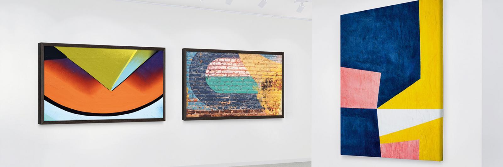 Photo und Art, bedruckbare Künsterleinwände und Fotopapiere drei farbige Kunstreproduktionen an der Wand einer Galerie