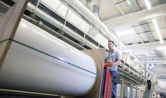 Umweltfreundliche Druckmedien - Gabelstapler mit weißer Jumborolle vor Produktionsanlage