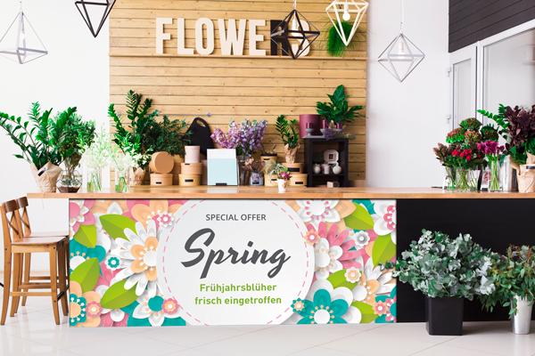 Umweltfreundliche Klebefolie Werbetechnik - Blumengeschäft mit grossflaechiger Fruehjahrsaktionswerbung auf schwarzer Theke