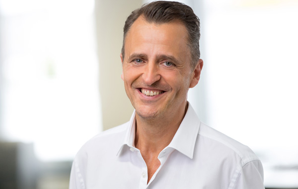 Umweltfreundliche Druckmedien - Portraitfoto dunkelhaariger Mann im weißen Hemd